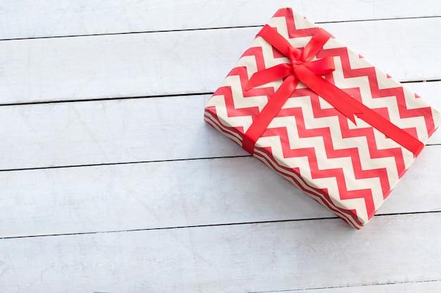 Geschenkbox mit rotem chevron-muster und schleife auf weiß. weihnachtsgeschenk und würdige belohnung am jubiläumsgeburtstag von weihnachten
