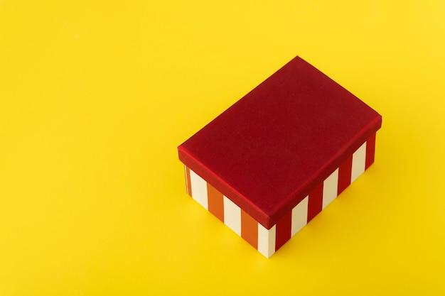 Geschenkbox mit rotem deckel auf gelbem hintergrund. festliche verpackung.