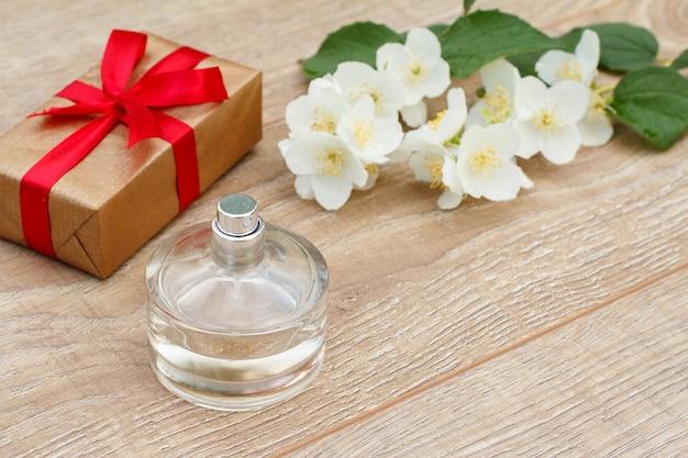 Geschenkbox mit roten bändern, parfüm und jasminblütenzweig auf den holzbrettern. konzept, an feiertagen ein geschenk zu machen. ansicht von oben.
