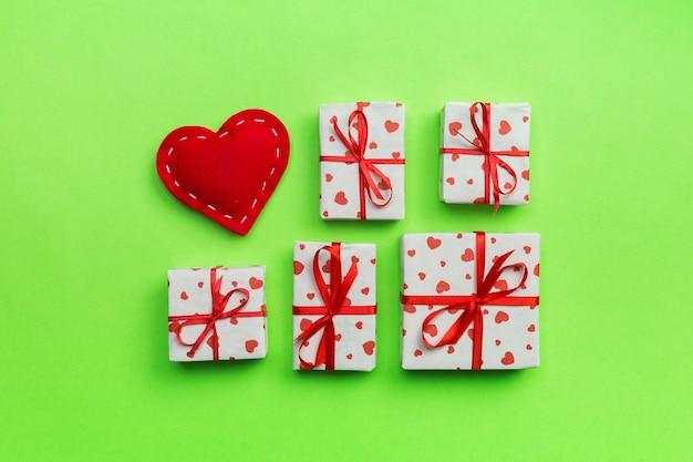 Geschenkbox mit roten herzen auf grünem hintergrund. draufsicht mit kopienraum