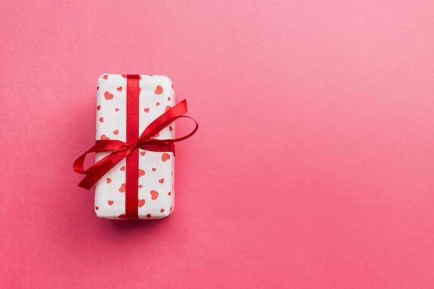Geschenkbox mit roten herzen auf koralle farbiger, draufsicht