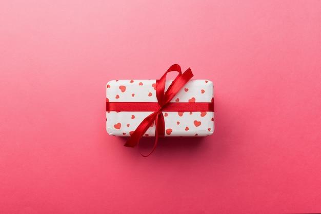 Geschenkbox mit roten herzen auf korallenrotem hintergrund.