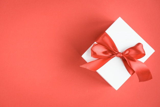 Geschenkbox mit roter schleife auf rot.