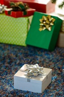 Geschenkbox mit roter schleife auf teppich in der nähe von spielzeug am weihnachtstag zu hause