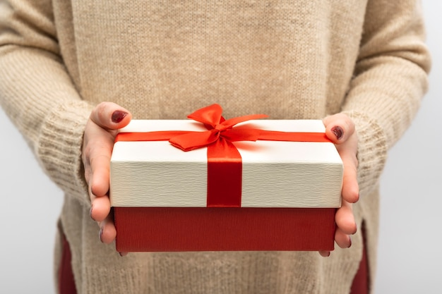 Geschenkbox mit roter schleife in weiblichen händen