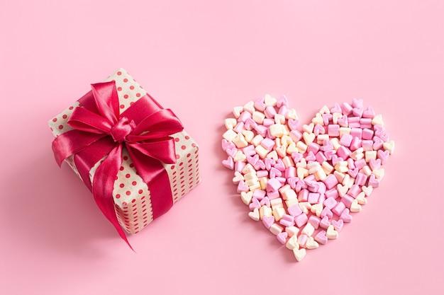 Geschenkbox mit roter schleife und herz aus bonbons auf rosa oberfläche