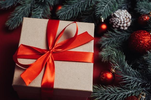 Geschenkbox mit roter schleife und weihnachtsbaumzweig auf rotem hintergrund.