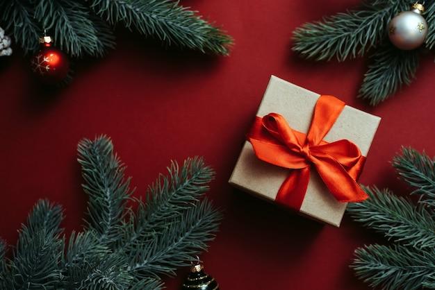 Geschenkbox mit roter schleife und weihnachtsbaumzweig mit kugeln auf rotem hintergrund.
