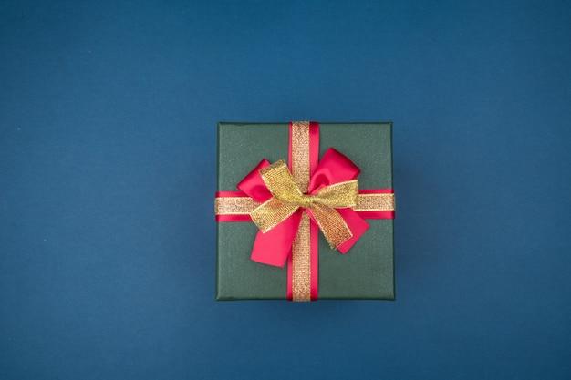 Geschenkbox mit roter und goldener schleife auf dunkelblauem hintergrund mit silbernen sternen. urlaubskonzept.