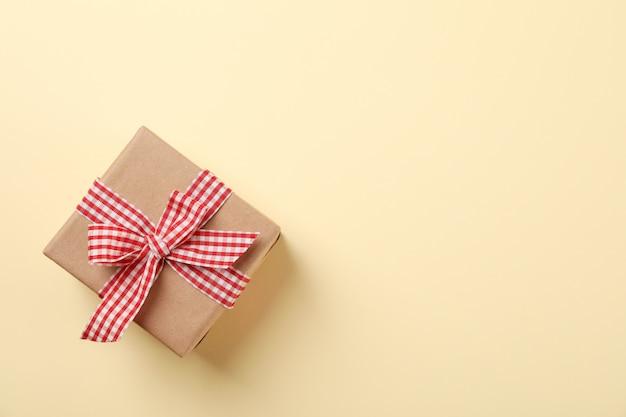 Geschenkbox mit schleife auf farbigem hintergrund, platz für text