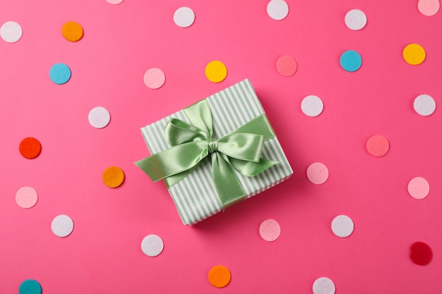 Geschenkbox mit schleife auf rosa hintergrund, platz für text
