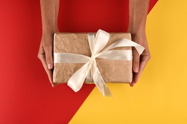 Geschenkbox mit schleife in den weiblichen händen auf gelb-rotem hintergrund.