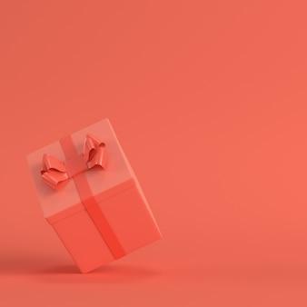 Geschenkbox mit schleife in lebender korallenfarbe. minimalismus-konzept