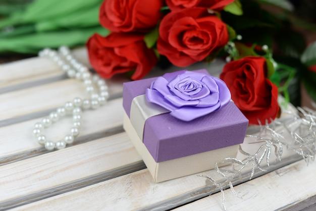 Geschenkbox mit schleife mit blumen aus roten rosen für valentinstag urlaub 8. märz muttertag auf hölzernen hintergrund