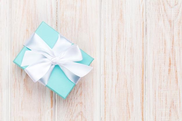 Geschenkbox mit schleife über weißem holztisch mit kopierraum