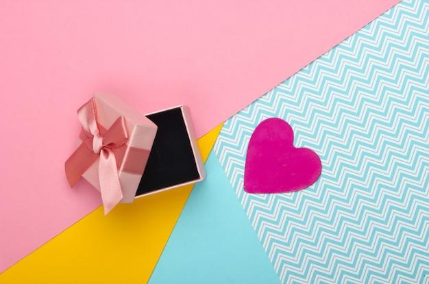 Geschenkbox mit schleife und dekorativem herzen auf einem farbigen hintergrund. valentinstag. pastellfarbentrend. draufsicht