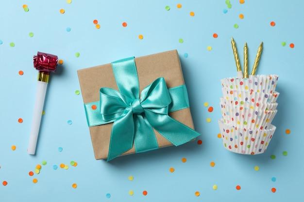 Geschenkbox mit schleife und geburtstagszubehör auf blauem hintergrund, draufsicht