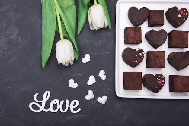 Geschenkbox mit schokoladenbonbonherzen und tulpen auf dunklem hintergrund. wüste zum valentinstag