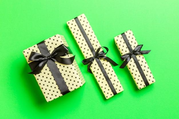 Geschenkbox mit schwarzem bogen für weihnachten oder neujahr auf grünem hintergrund, draufsicht