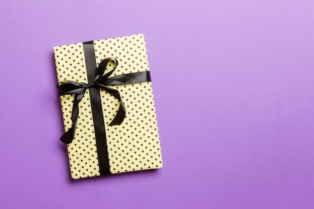 Geschenkbox mit schwarzem bogen für weihnachten oder neujahr auf lila