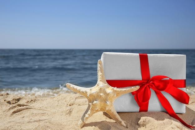 Geschenkbox mit seestern am strand. weihnachtsferienkonzept