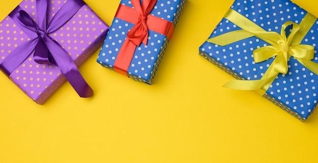 Geschenkbox mit seidenband auf gelbem hintergrund gebunden, ansicht von oben. festliche kulisse, kopierraum