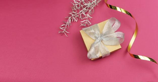 Geschenkbox mit silberner schleife und goldenem serpentin