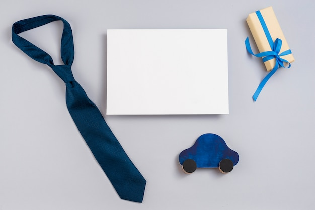 Geschenkbox mit spielzeugauto, papier und krawatte