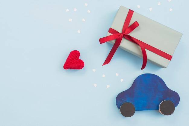 Geschenkbox mit spielzeugauto und rotem herzen