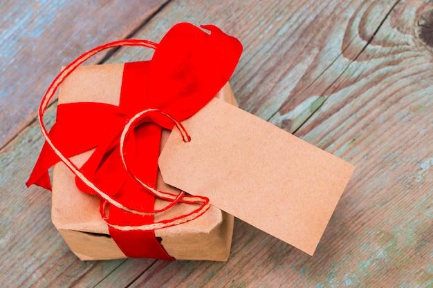Geschenkbox mit tag mit leerem platz für einen text auf holzhintergrund.