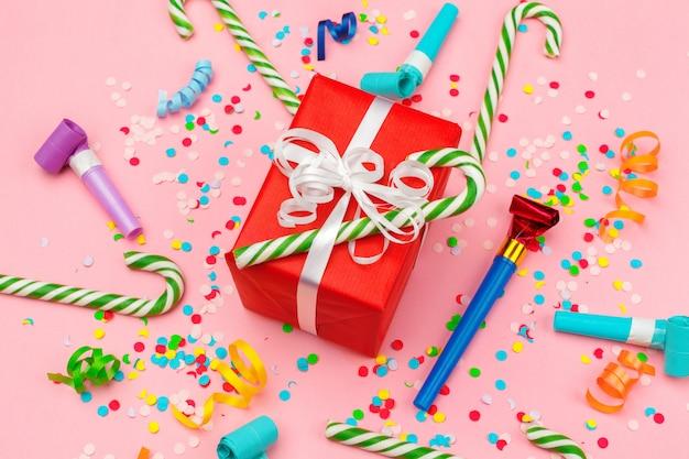 Geschenkbox mit verschiedenen partykonfetti, luftschlangen und dekoration