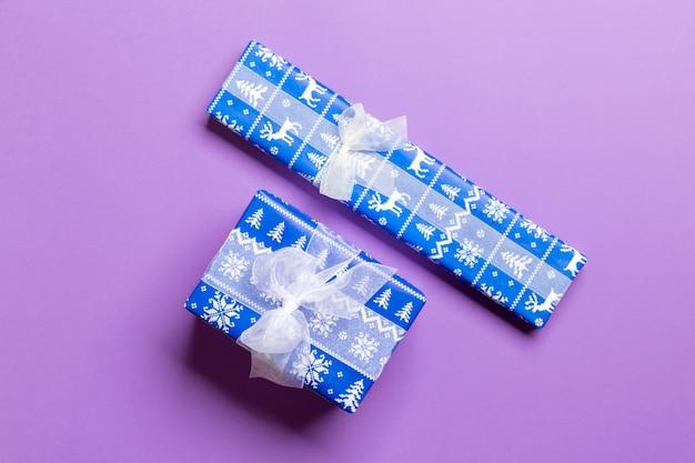 Geschenkbox mit weißem bogen für weihnachten oder neujahr auf purpurrotem hintergrund, draufsicht