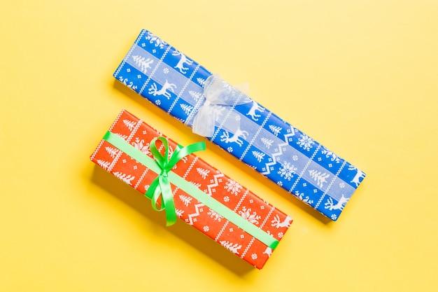 Geschenkbox mit weißem und grünem bogen für weihnachten auf gelb
