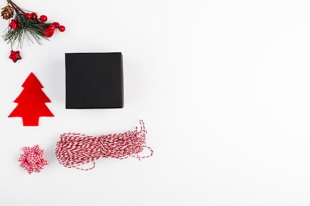 Geschenkbox nahe bogen, tannenzweig und threads