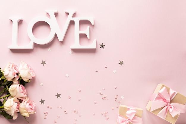 Geschenkbox oder geschenkbox und blumen auf rosa tischoberansicht.