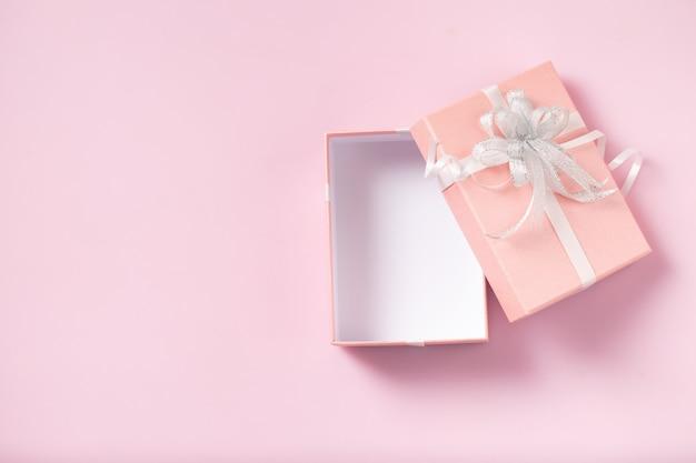 Geschenkbox offen leer auf rosa hintergrund