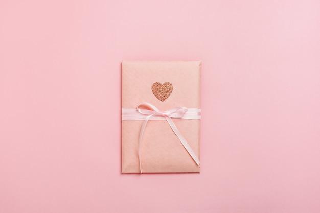 Geschenkbox-paket mit herz auf pastellrosa hintergrund.