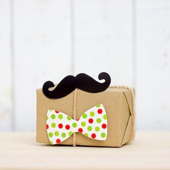 Geschenkbox, papierschnurrbart, bindung auf hölzernem hintergrund mit kopienraum. alles gute zum vatertag.