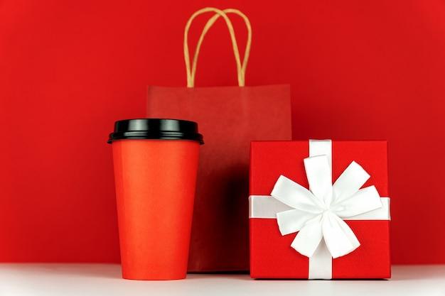 Geschenkbox, papiertüte und kaffeetasse auf rotem raum