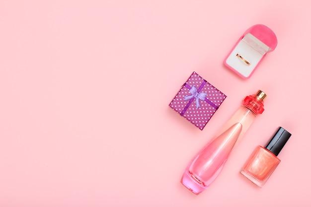 Geschenkbox, parfümflasche, nagellack und goldener ring in box auf rosafarbenem hintergrund. damenkosmetik und accessoires. ansicht von oben.