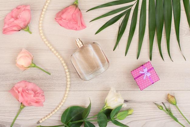 Geschenkbox, parfümflasche, perlen an einer schnur, weiße und rosa blüten, grüne blätter auf holzhintergrund. damenkosmetik. ansicht von oben.