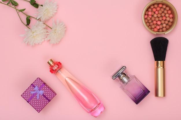 Geschenkbox, parfümflaschen, pinsel, pulver und blumen auf rosafarbenem hintergrund. damenkosmetik und accessoires. ansicht von oben.