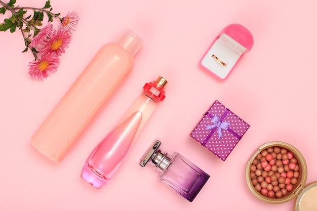 Geschenkbox, parfümflaschen, shampoo, pulver und goldener ring in box auf rosafarbenem hintergrund. damenkosmetik und accessoires. ansicht von oben.