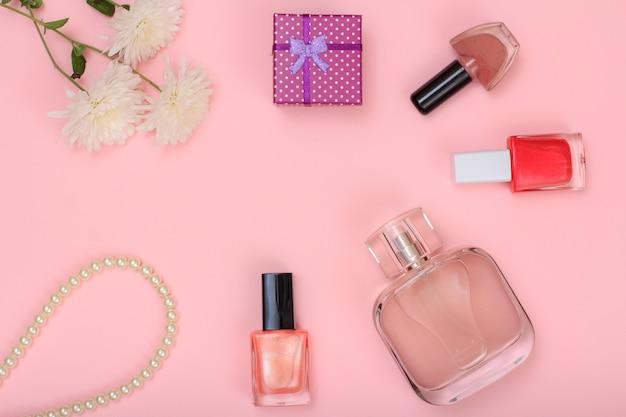 Geschenkbox, perlen, parfümflasche, flaschen mit nagellack und blumen auf rosafarbenem hintergrund. damenkosmetik und accessoires. ansicht von oben.