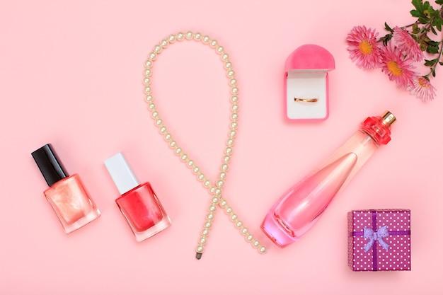 Geschenkbox, perlen, parfümflasche, nagellack und goldener ring in box auf rosafarbenem hintergrund. damenkosmetik und accessoires. ansicht von oben.