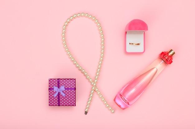Geschenkbox, perlen, parfümflasche und goldener ring in box auf rosafarbenem hintergrund. damenkosmetik und accessoires. ansicht von oben.