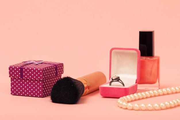 Geschenkbox, pinsel, ring in einer box, nagellack und perlen auf rosa hintergrund. damenschmuck, kosmetik und accessoires.