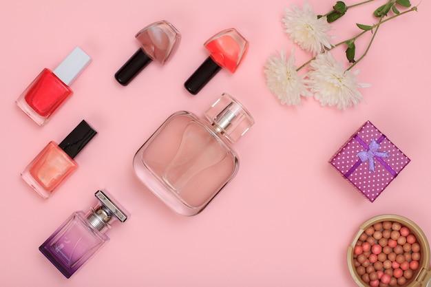 Geschenkbox, pulver, nagellack, parfümflaschen, lippenstift, pinsel und blumen auf rosafarbenem hintergrund. damenkosmetik und accessoires. ansicht von oben.