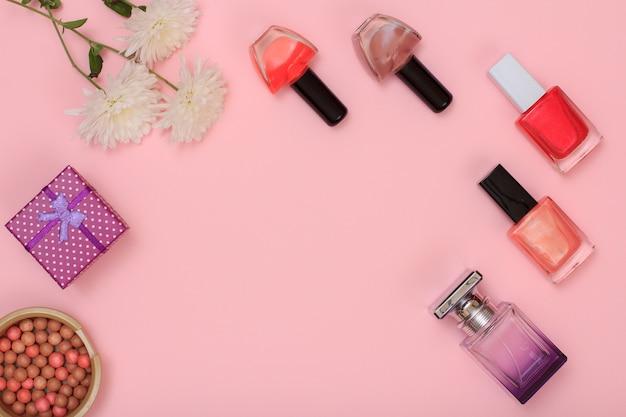 Geschenkbox, pulver, parfüm- und nagellackflaschen und blumen auf rosafarbenem hintergrund. damenkosmetik und accessoires. ansicht von oben.