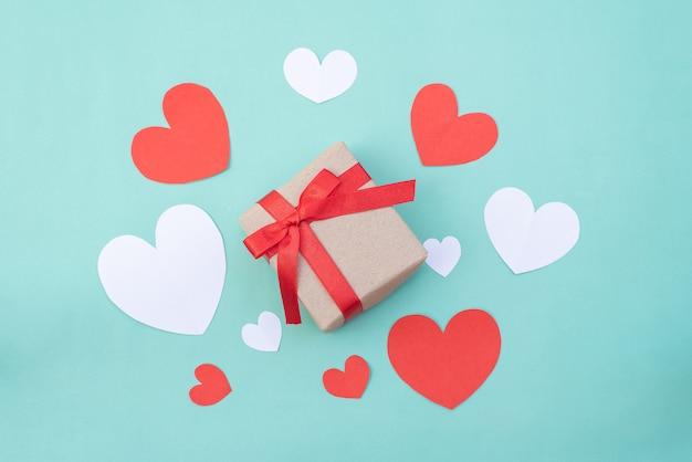 Geschenkbox, rote und weiße herzen auf blauem pastellhintergrund. valentinstag oder hochzeitszeremonie konzept